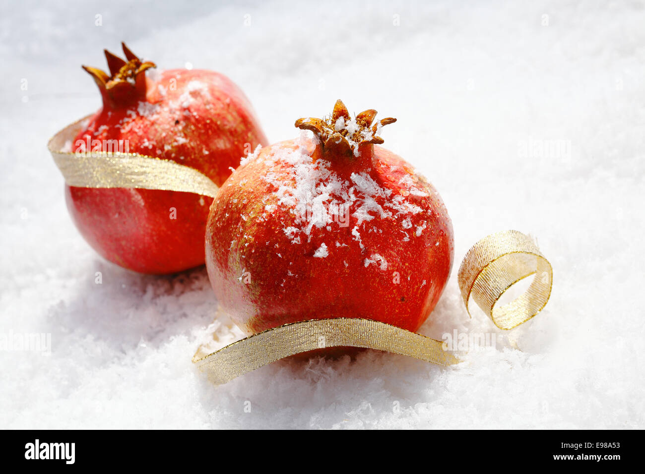Vivid red Christmas pomegranates dusted with snowflakes lying in fresh winter snow with a decorative gold ribbon - Stock Image
