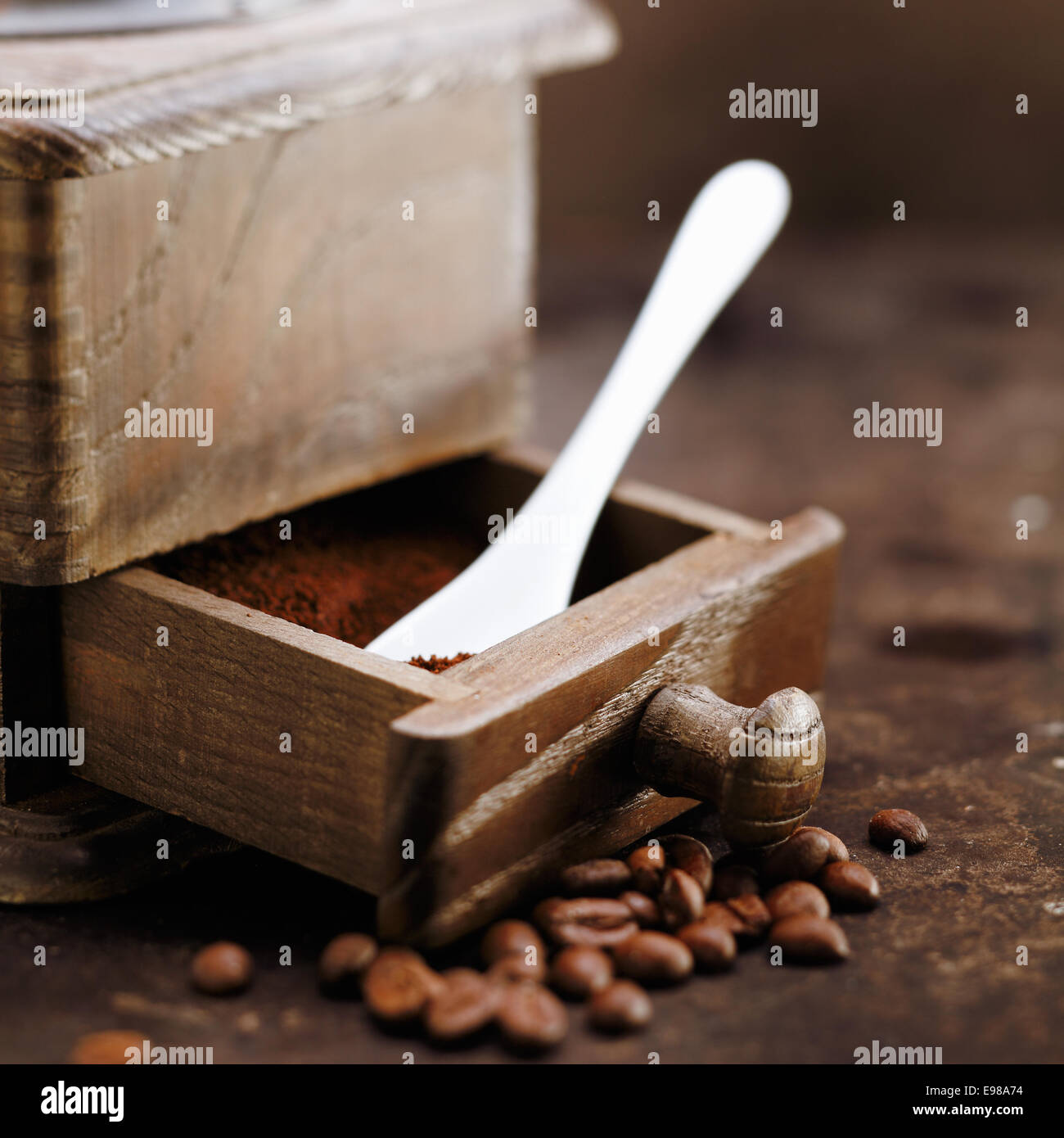 Freshly ground coffee and a measuring spoon in the open drawer of an old retro wooden grinder - Stock Image
