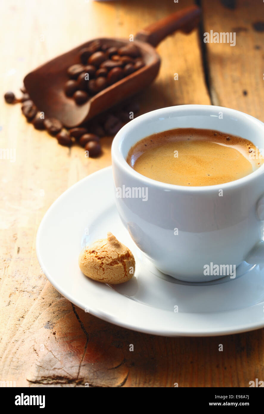 Strong aromatic espresso coffee served in a small cup with a macaroon on the side and a scoop of coffee beans in - Stock Image