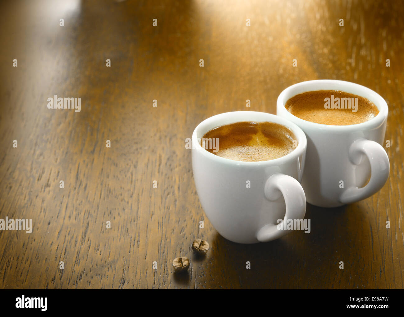 Two cups of freshly brewed espresso coffee with two single coffee beans on a textured wooden table top with copyspace - Stock Image