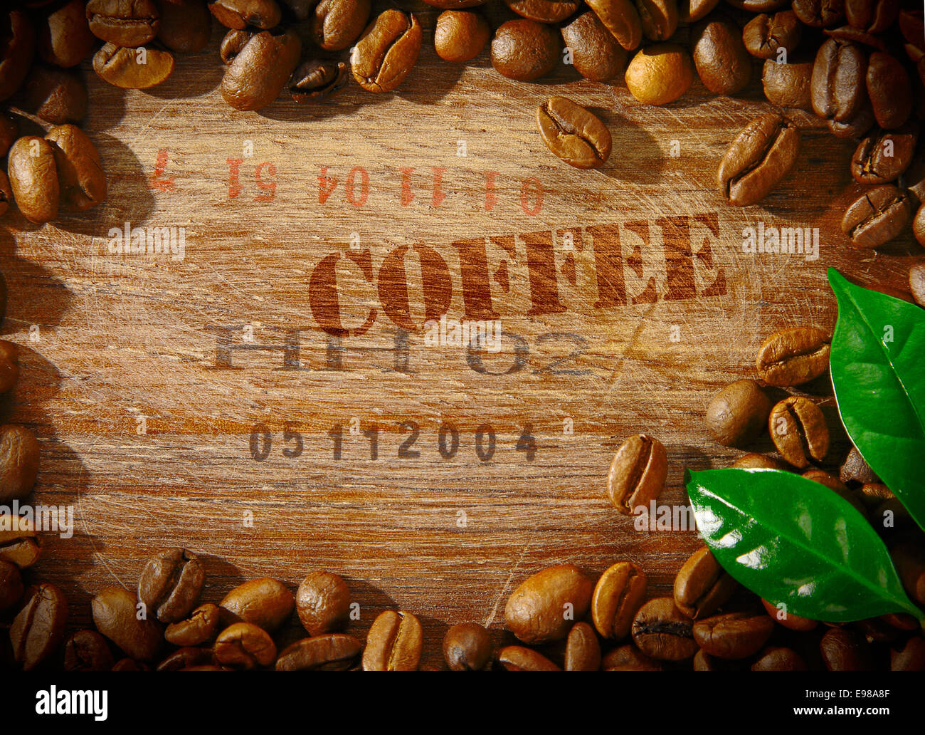 Fresh roasted coffee beans framing an old wooden board stamped with the word COFFEE and the shipment number of a Stock Photo