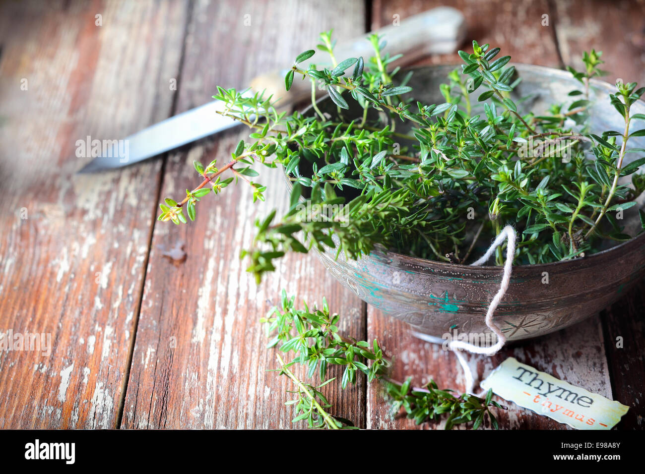 Old pottery bowl full of sprigs of fresh thyme with a