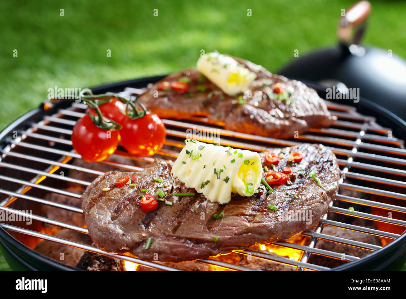 Succulent portion of lean steak topped with butter and herbs grilling on a grid over hot coals in a barbecue - Stock Image