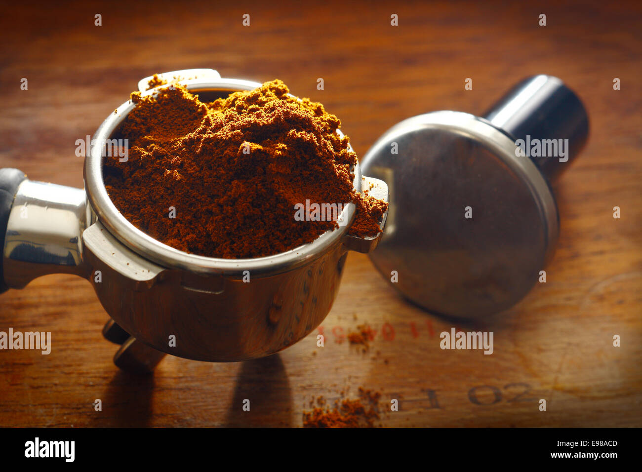 Freshly ground coffee overflowing over the rim of a metal filter onto a wooden surface with measuring spoon - Stock Image