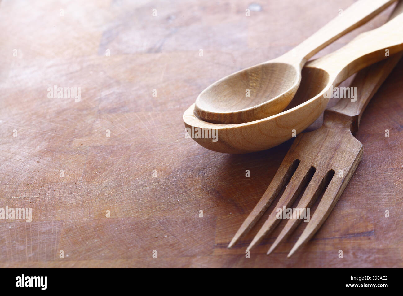 Handcrafted wooden kitchen utensils with a fork and spoons in two sizes lying on a wood surface with copyspace - Stock Image