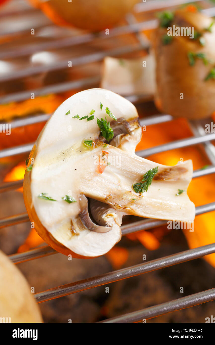 Fresh halved mushrooms sprinkled with chopped herbs for flavouring grilling over a barbecue fire Stock Photo