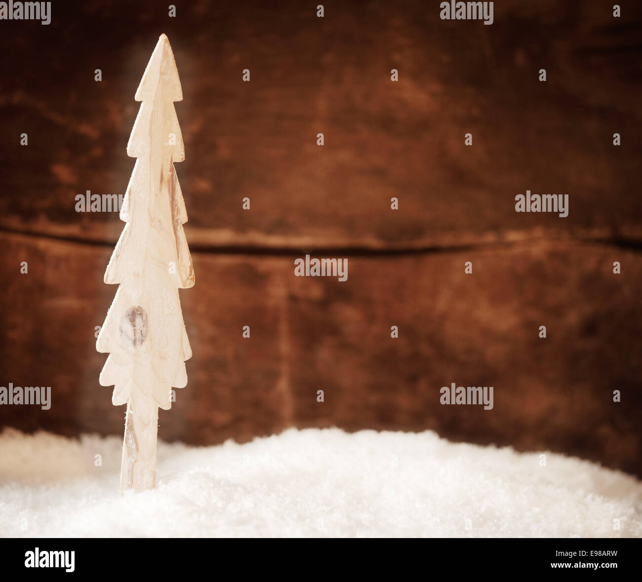 Stylised wooden Christmas tree standing in fresh winter snow in front of a rustic timber wall with copyspace for - Stock Image
