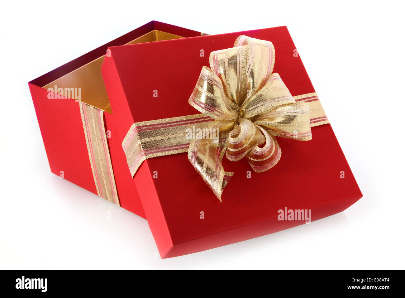 open gift box with tilted lid and decorative gold ribbon and bow for celebrating christmas valentines birthday or an anniversary close up view on a white