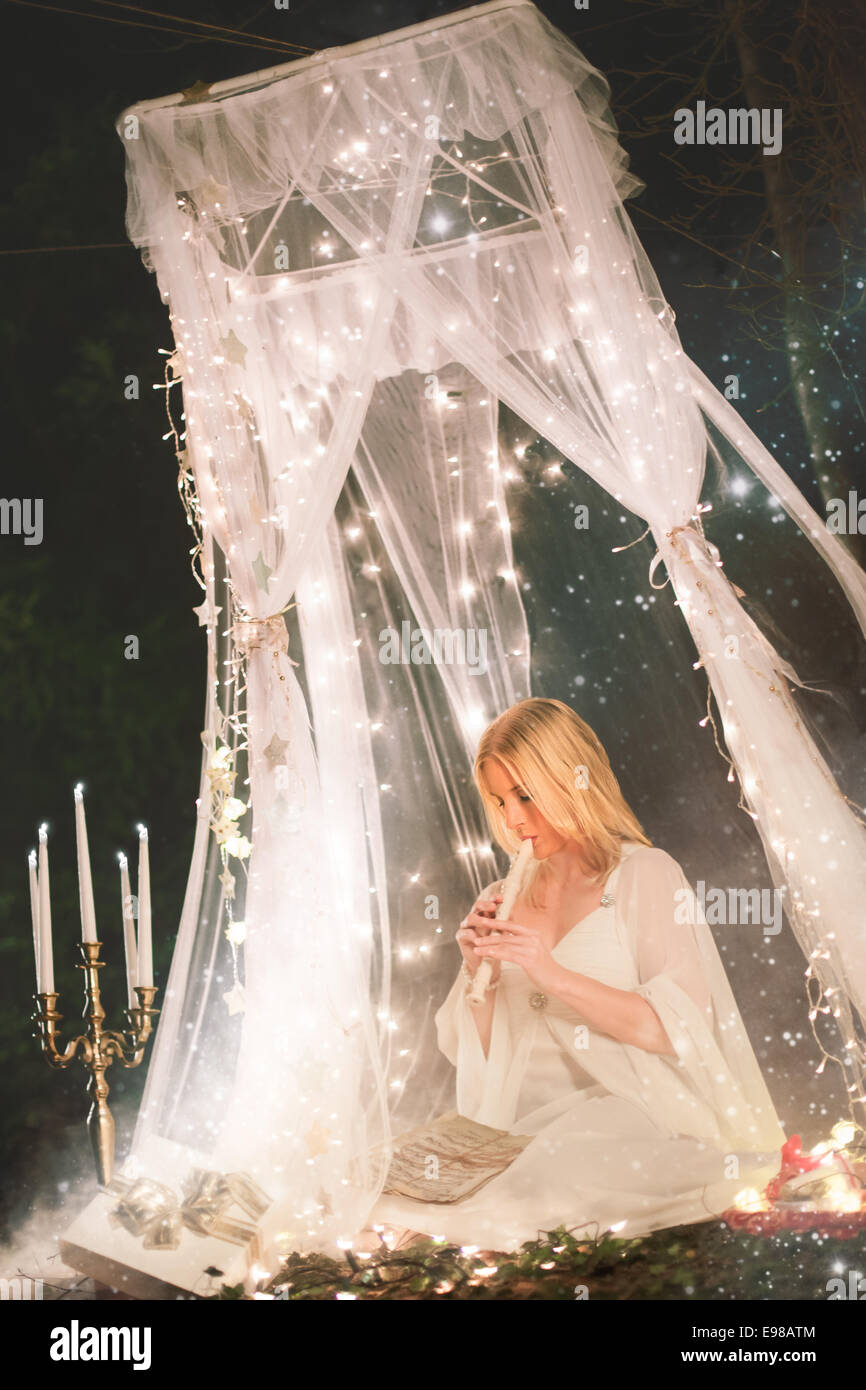 Beautiful Christmas angel in a forest sitting under a white lace canopy surrounded by stars, glowing candles and Stock Photo