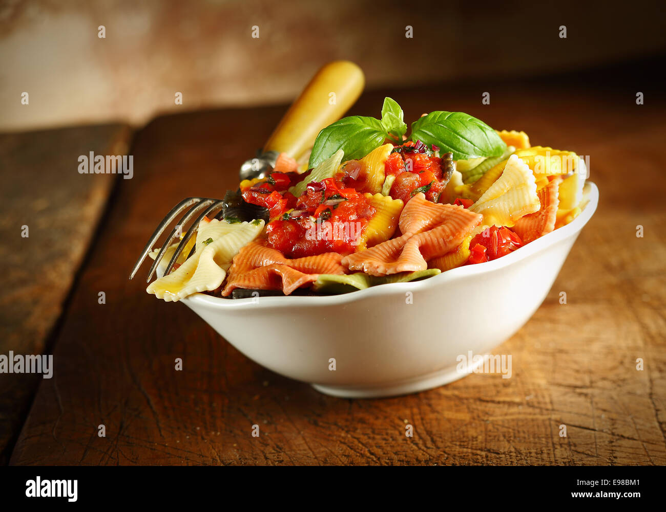Delicious colourful Italian bow tie pasta served with tomato and basil in a white ceramic dish with a fork on an - Stock Image