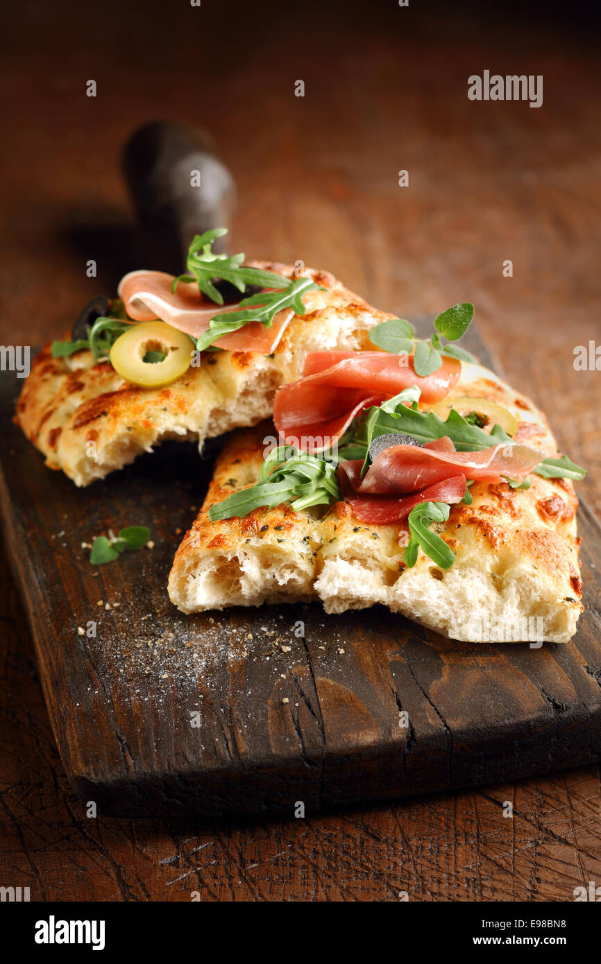 Freshly baked traditional savoury Italian focaccia bread topped with ham and olives and garnished with fresh rocket - Stock Image