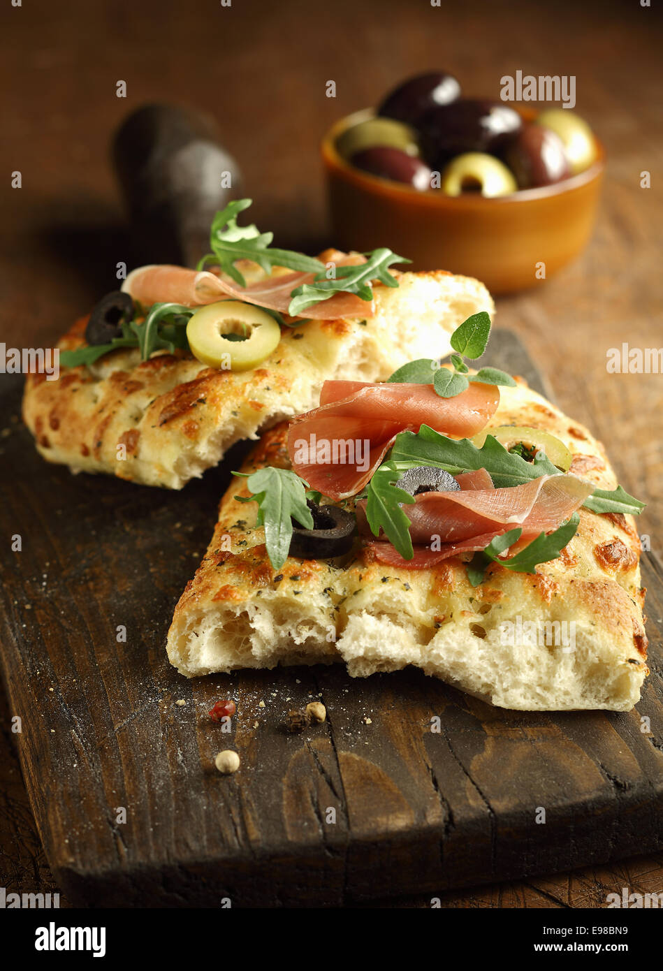 Delicous traditional oven-baked Italian focaccia bread topped with ham, rocket and olives on old cracked wooden - Stock Image