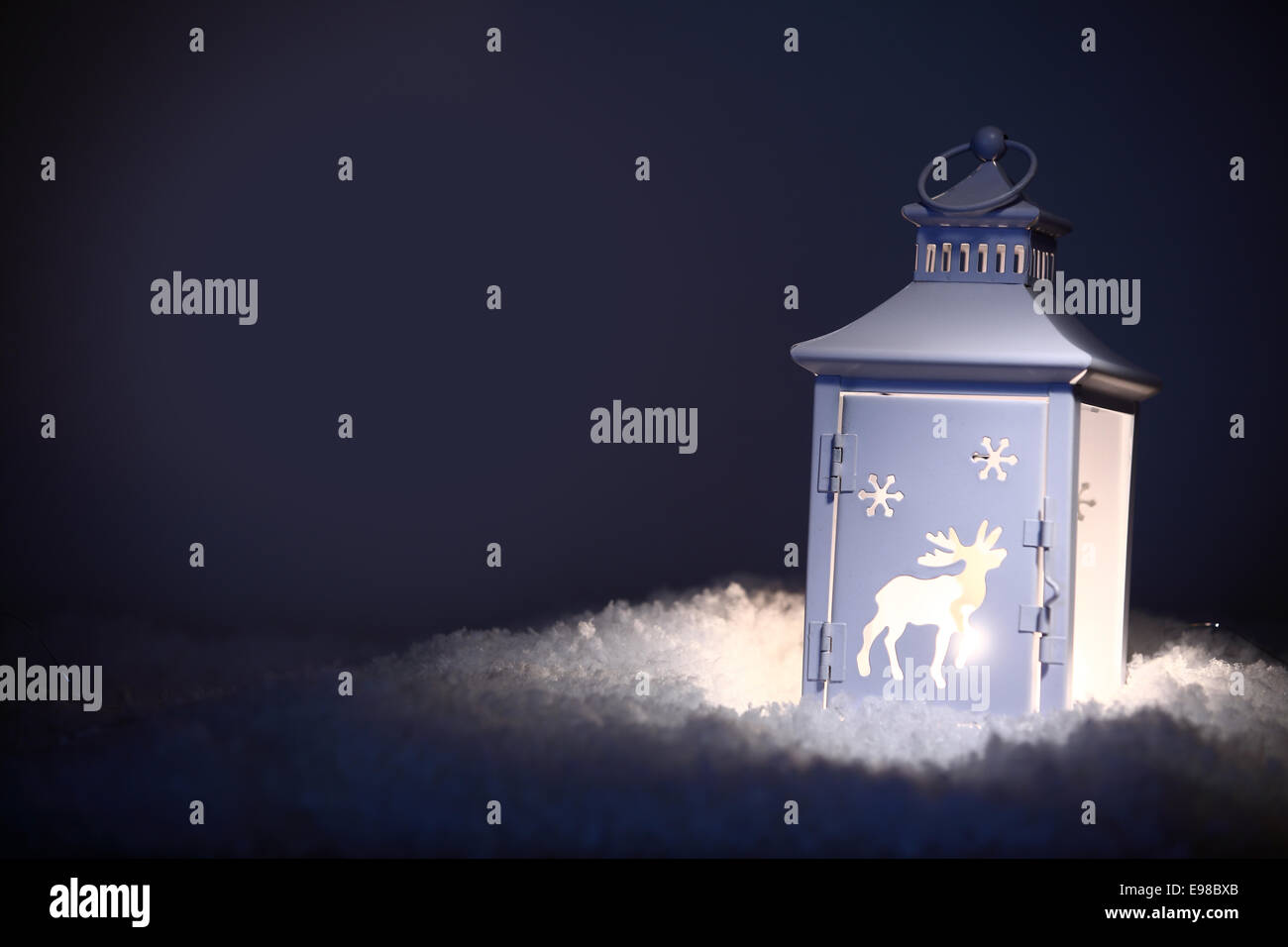 Decorative Christmas lantern standing on a bed of fresh winter snow shining in the night as a guiding light, with - Stock Image