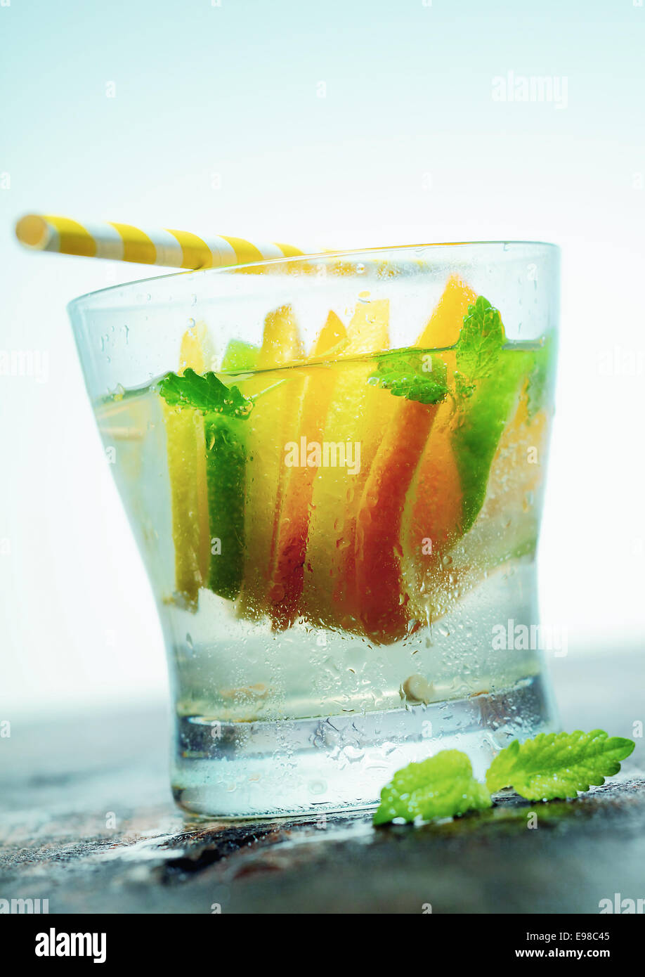 Glass of refreshing iced vodka or gin with slices of tangy citrus and fresh leaves of mint served on an old wooden - Stock Image
