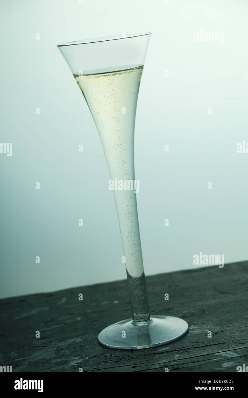 champagne, sparkling wine flute in a stylish tall fluted glass served on an old wooden bar counter, tilted angle - Stock Image