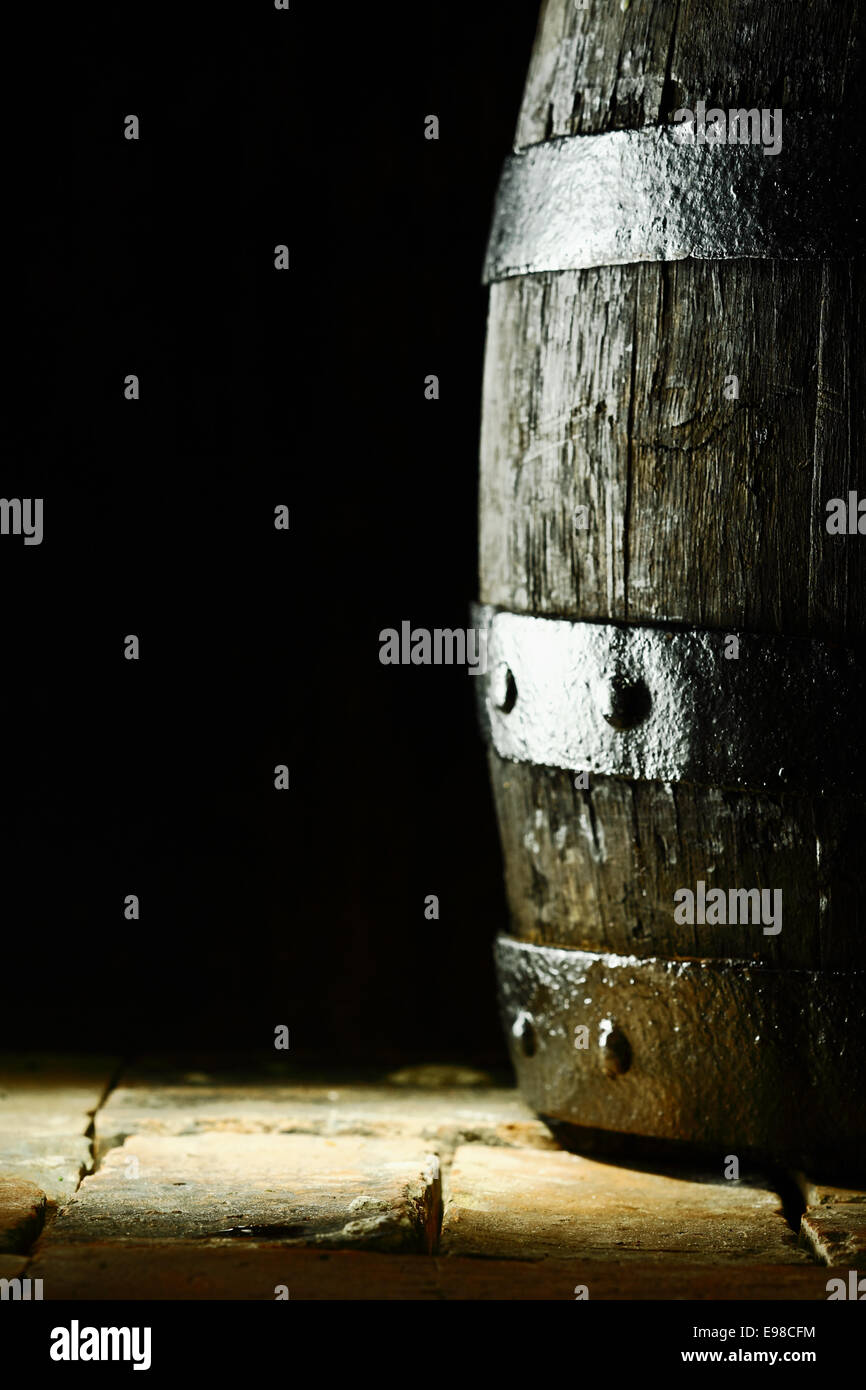 Old oak barrel standing upright on flagstones or old bricks with a dark background and copyspace conceptual of the - Stock Image