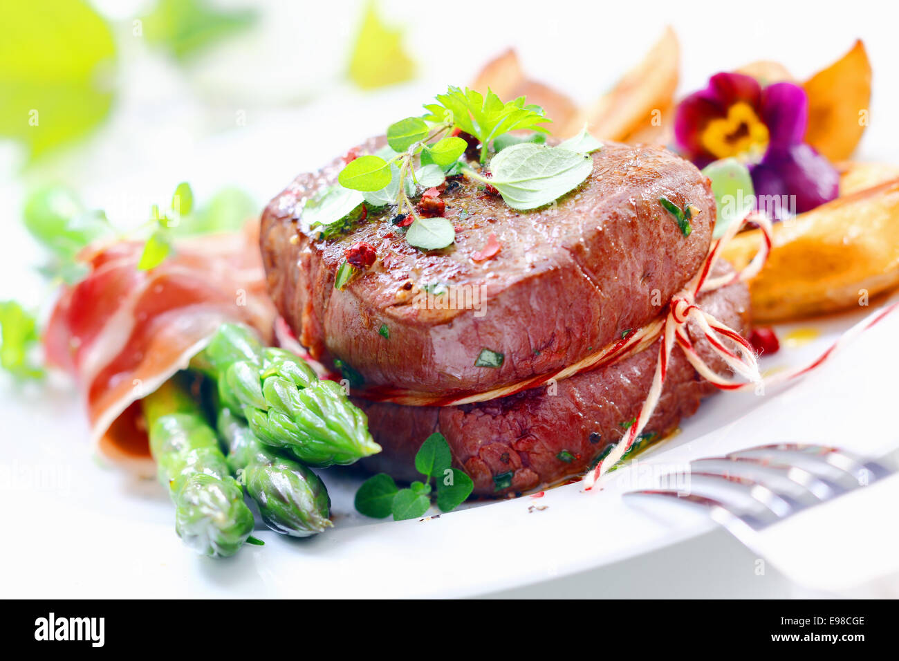 Thick juicy steak with fresh green asparagus spears wrapped in thinly sliced ham or bacon served garnished with - Stock Image