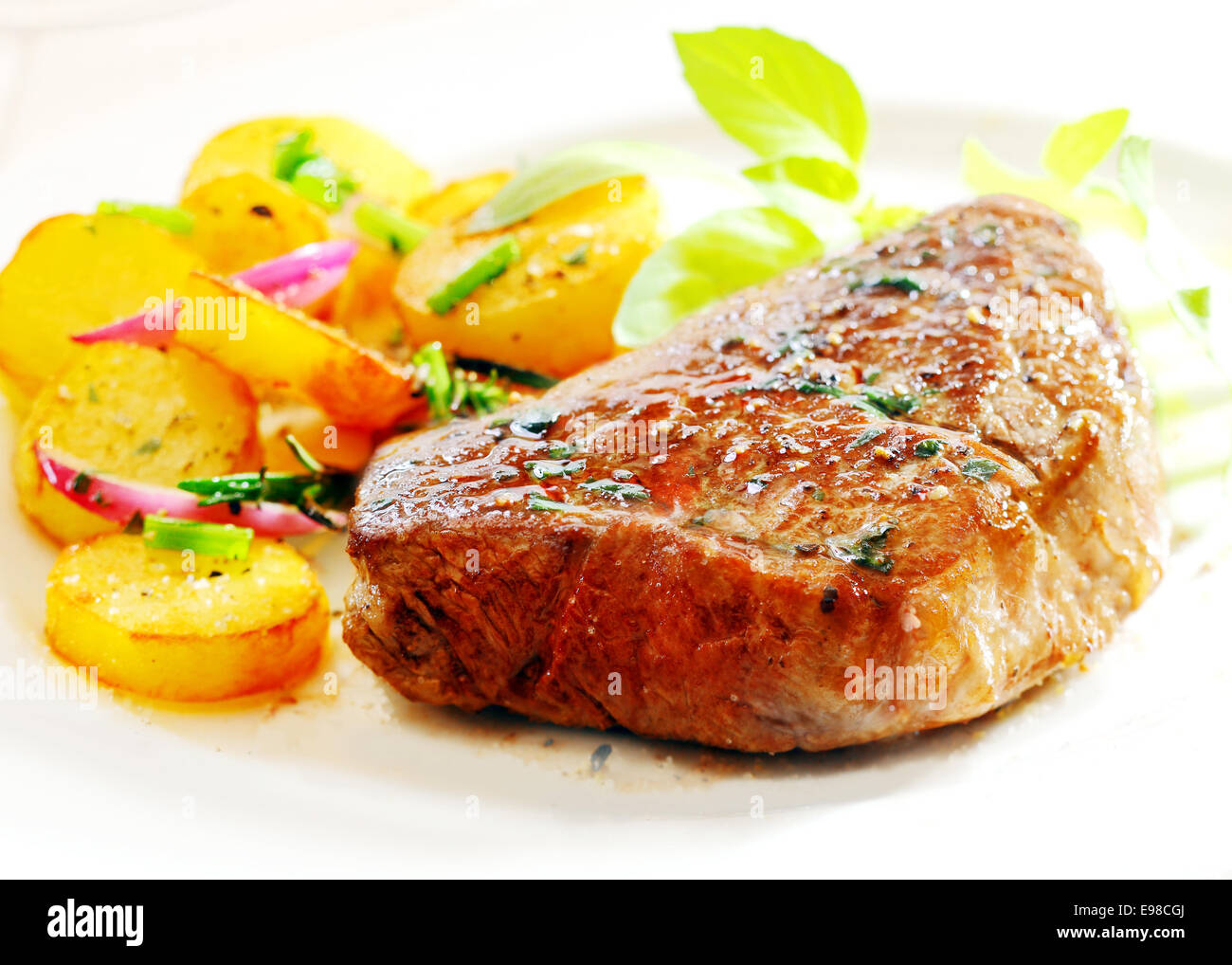 Large portion of thick juicy steak with crisp golden roast potatoes, onion and fresh herbs on a white plate, closeup - Stock Image