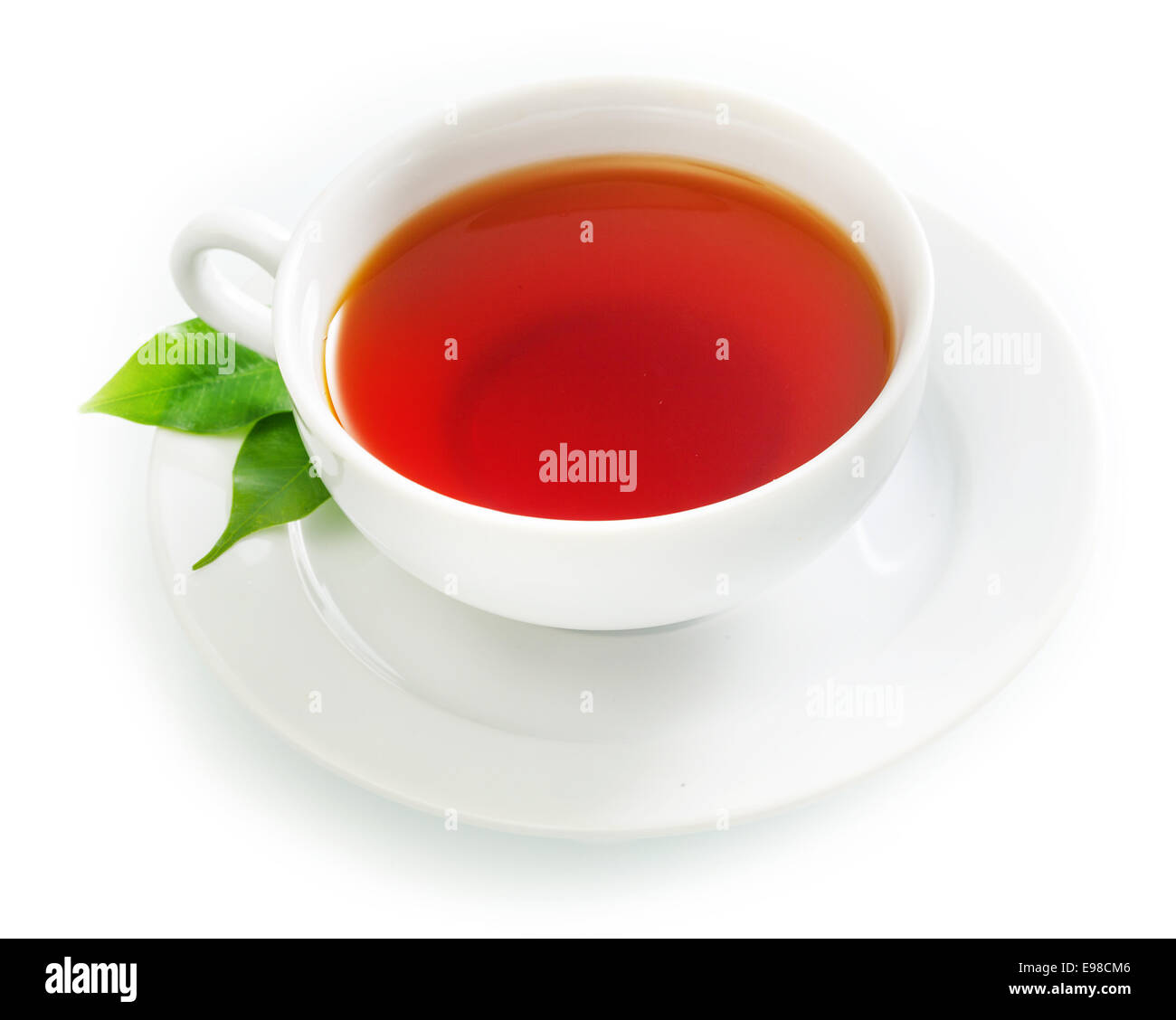 Cup of fresh hot black tea in an elegant plain white cup and saucer with fresh green tea leaves over a white background - Stock Image
