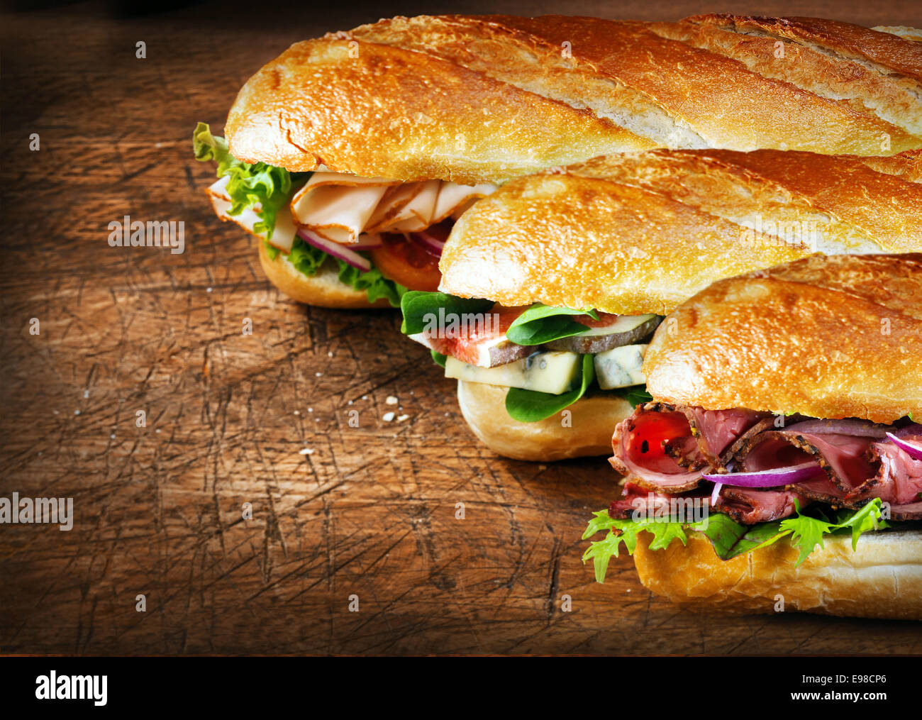 Three tasty baguettes with savory fillings lined up on a rustic wooden countertop with roast beef and rocket, figs - Stock Image