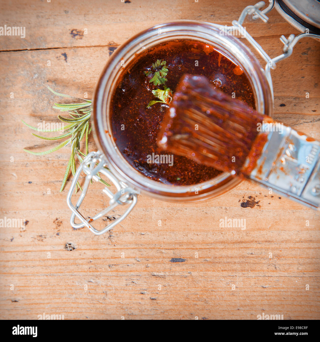 Overhead view of an open jar of savory spicy basting sauce with a basting brush and sprig of fresh rosemary on a - Stock Image