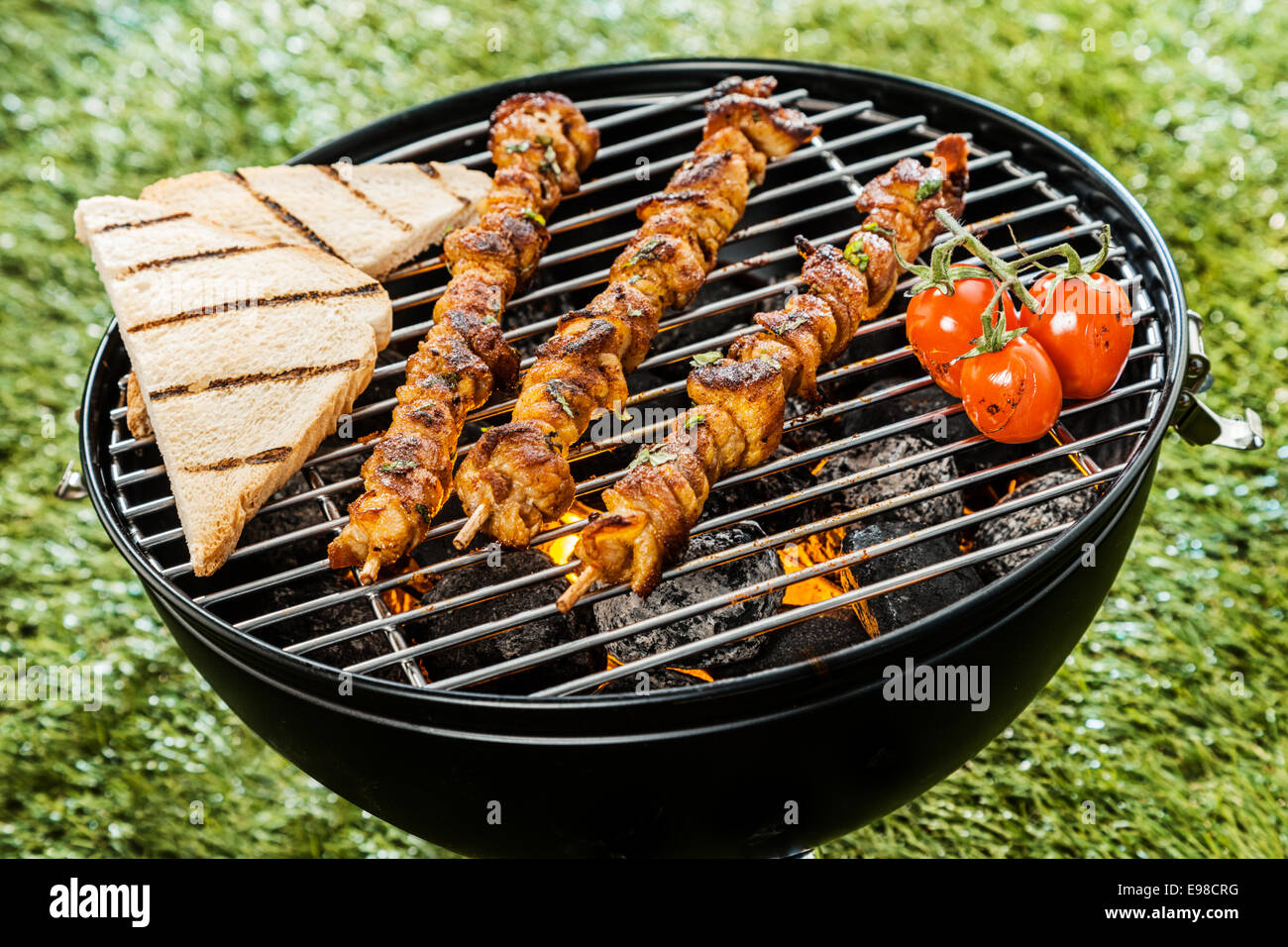 Three delicious meat kebabs grilling on a BBQ fire with slices of toast and tomatoes during a summer picnic in the Stock Photo