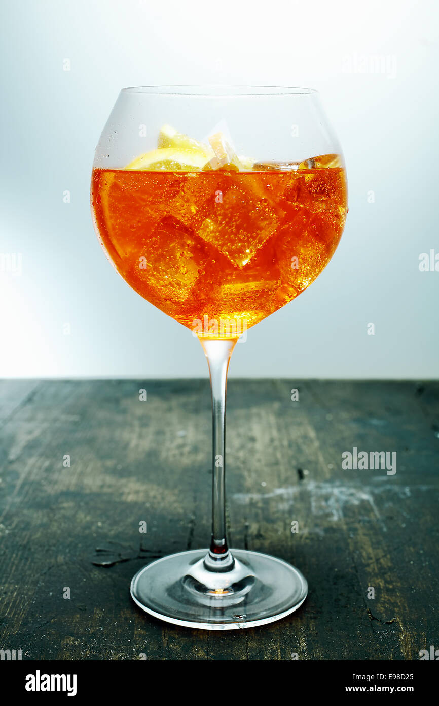 Chilled tropical aperol, rum and orange cocktail in an elegant wine glass standing on a wooden counter in a bar - Stock Image