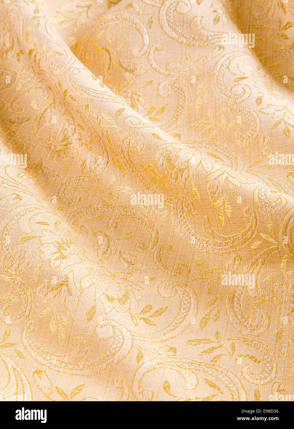 Soft folds of draped gold damask with a shiny floral pattern for a luxurious background of textiles used for interior - Stock Image