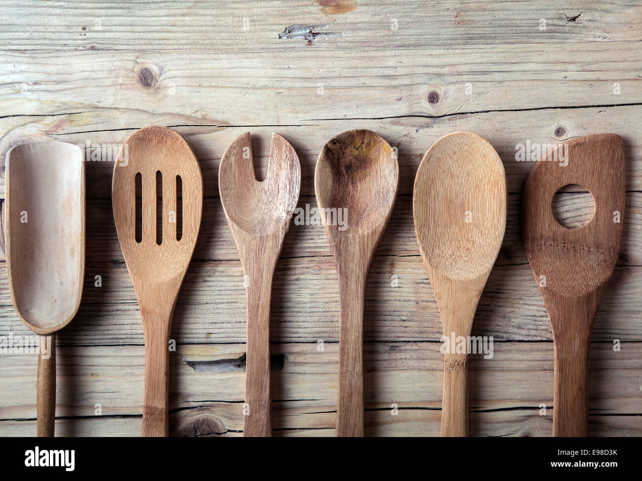 Row of assorted old wooden kitchen utensils lying on a grungy cracked wooden surface in a country kitchen - Stock Image