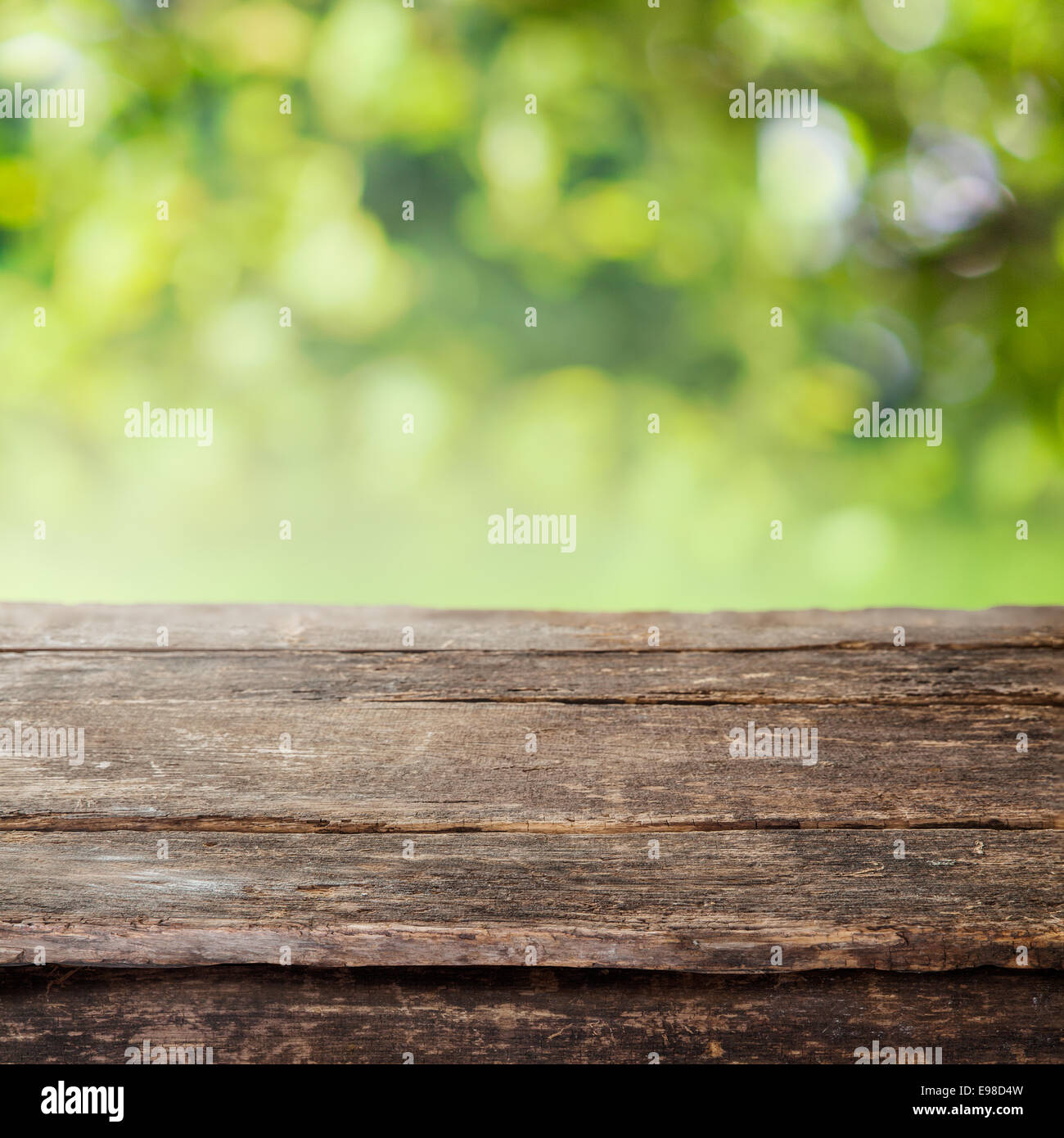 Rustic Weathered Cracked Wooden Country Fence Plank Or Table Top Against A Blurred Background Of Greenery And Foliage In Summer