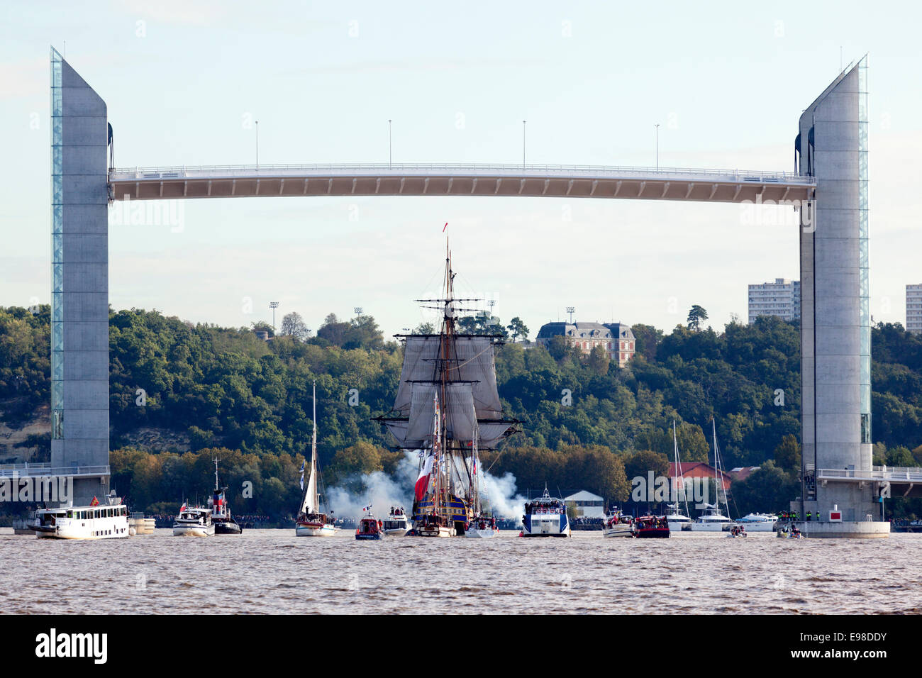 The replica of the frigate 'l'Hermione' (under the Chaban Delmas vertical-lift bridge) firing a salute - Stock Image