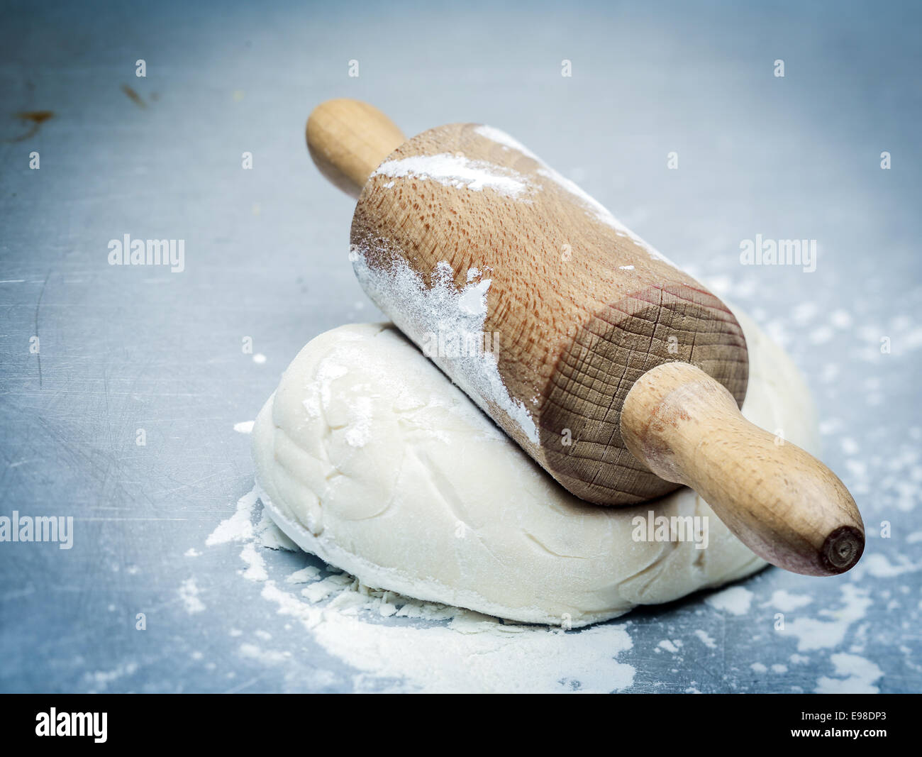 Mound of dough that has been allowed top rise topped with an old-fashioned wooden rolling pin ready to be flattened - Stock Image
