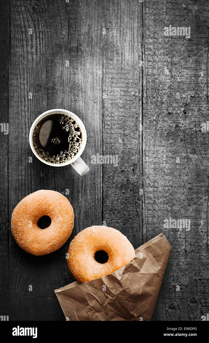 Freshly baked sugared ring doughnuts with a mug of full roast filter coffee and brown paper packaging on a grungy - Stock Image