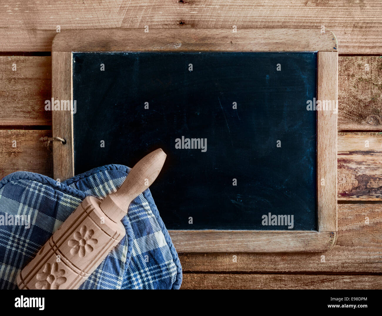 Decorative wooden rolling pin carved with patterns of flowers lying on a blue and white cloth on an blank old grunge Stock Photo