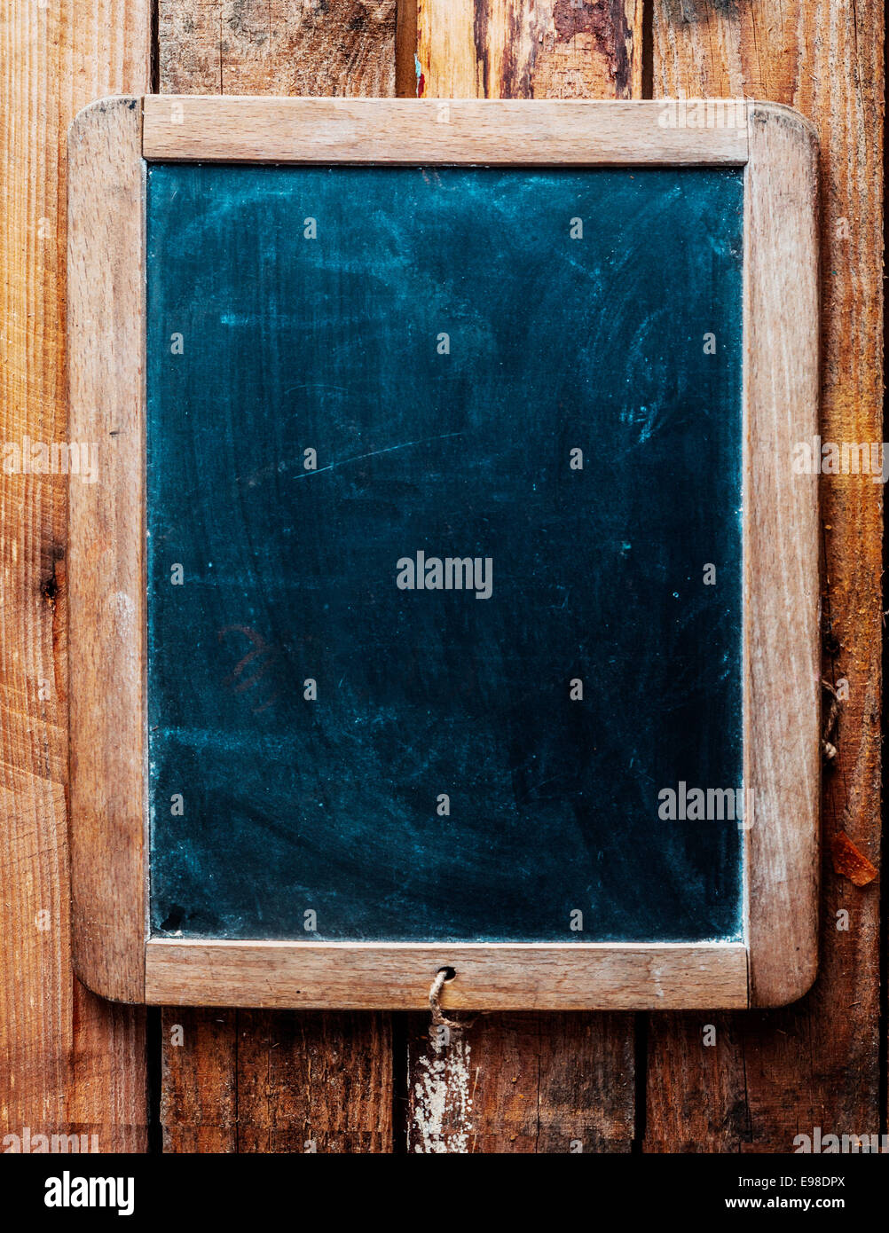 Vintage style wood framed chalkboard over old wood background. Space for insertion of your own text. - Stock Image