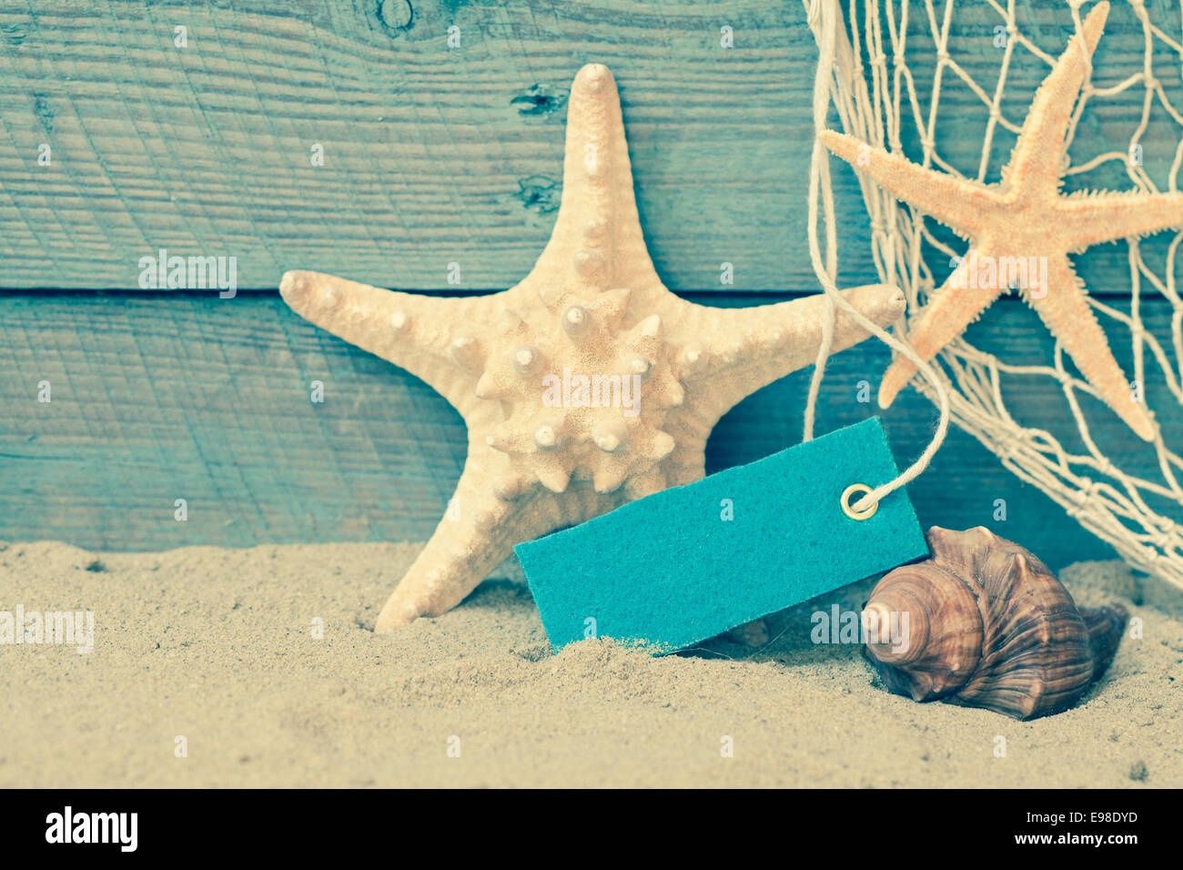 Toned Retro Nautical Background With Starfish And A Seashell On Beach Sand Against Rustic Blue Wooden Boards Blank Label