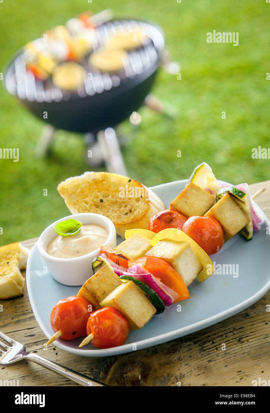 Outdoors Summer bbq smoked tofu on a table with a tofu kebab and a grill in the background - Stock Image