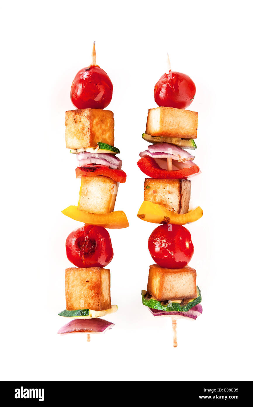 Two colorful healthy grilled smoked tofu and vegetable kebabs on wooden skewers with cherry tomato, pepper and onion - Stock Image