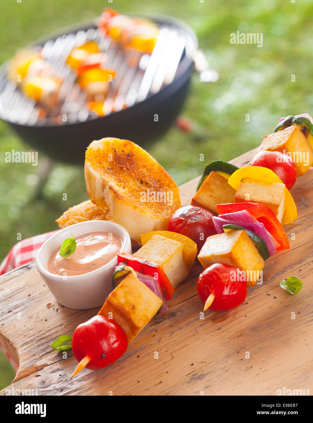 smoked Tofu and vegetable kebabs served with toasted slices of baguette and sauce on an outdoor picnic table at - Stock Image