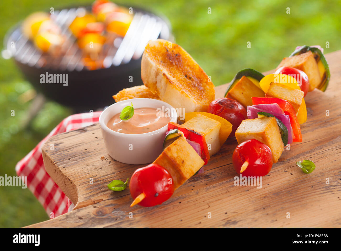 Healthy picnic lunch at a summer barbecue with grilled smoked Tofu and vegetable kebabs served with a savory sauce - Stock Image