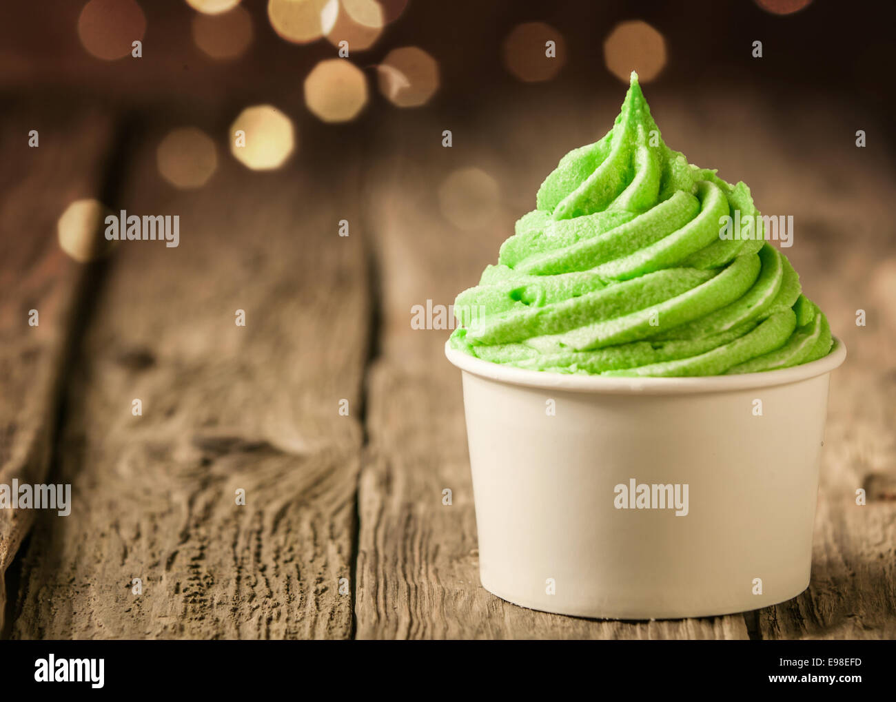 Tub of twirling creamy green Italian ice cream on a rustic wood table with a sparkling bokeh of party lights - Stock Image