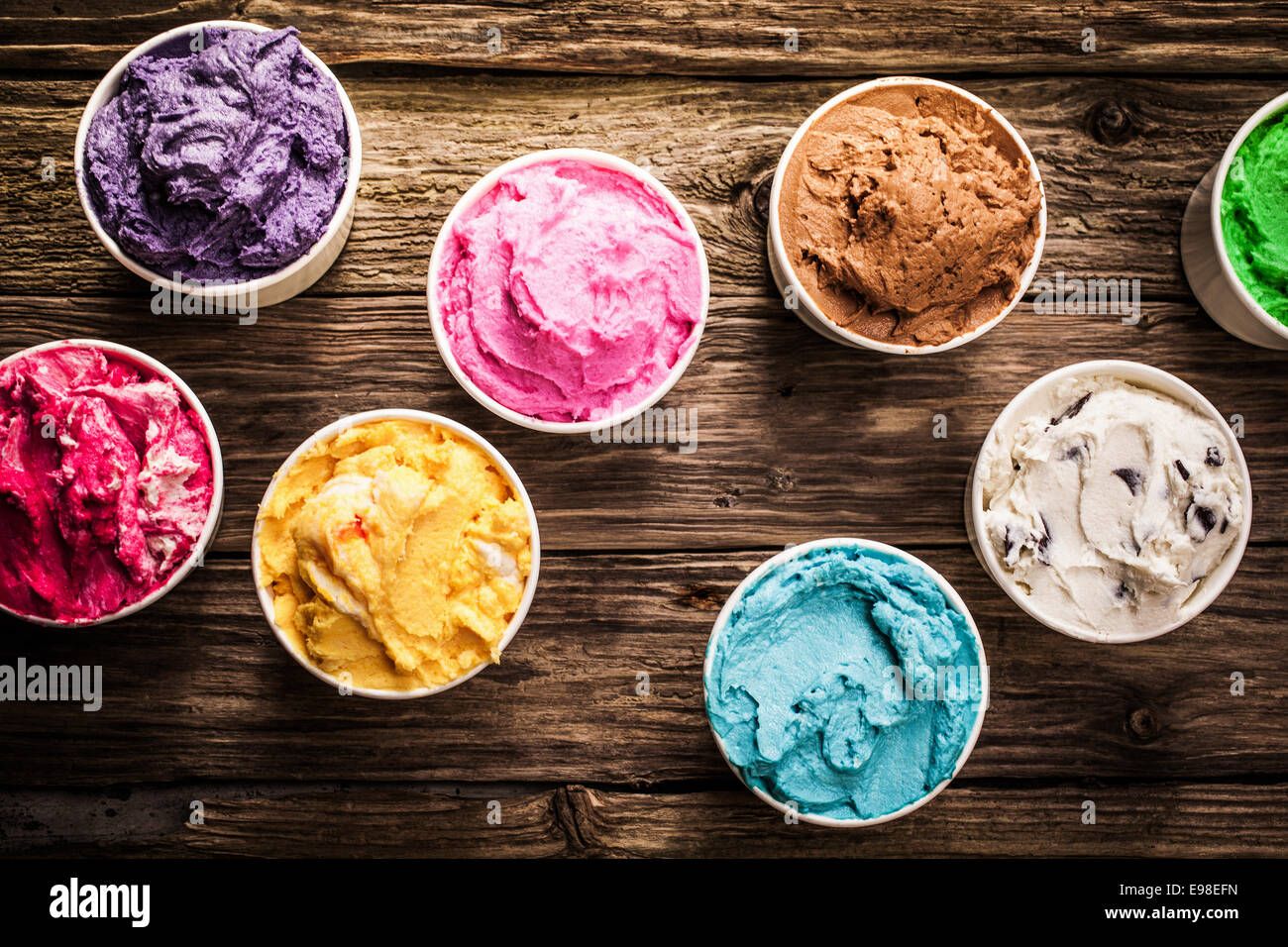 Selection of gourmet flavours of Italian ice cream in vibrant colors served in individual plastic tubs on an old Stock Photo