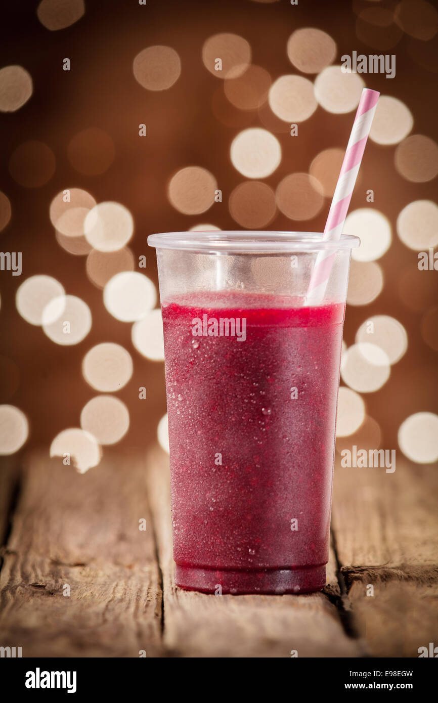 Glass of healthy blueberry smoothie served on an old rustic wooden taable against a festive background bokeh of - Stock Image
