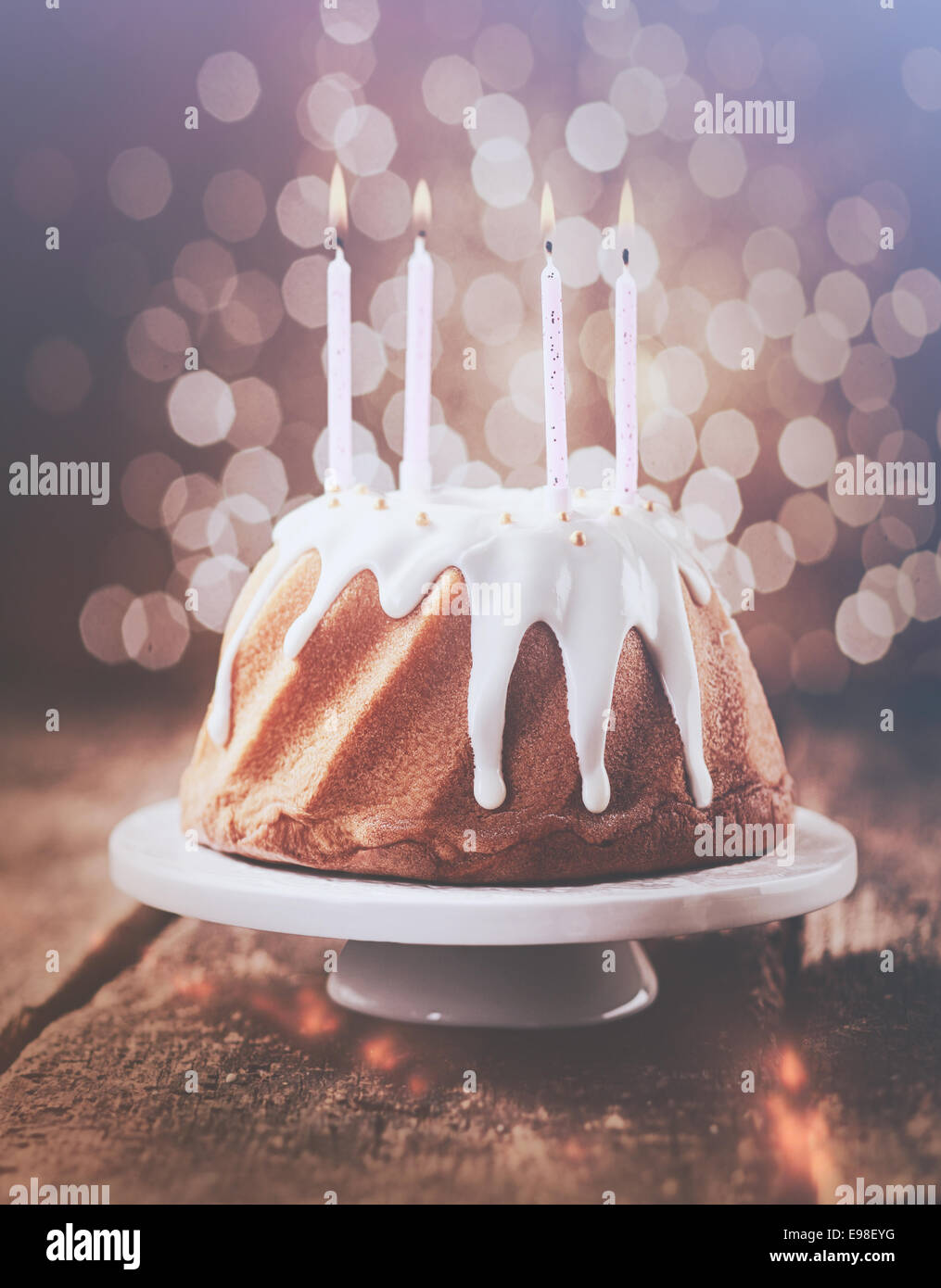 Retro Vintage Effect Birthday Cake Glazed With Dripping White Icing Decorated Pearls And Topped Four Burning Party Candles A Background Bokeh