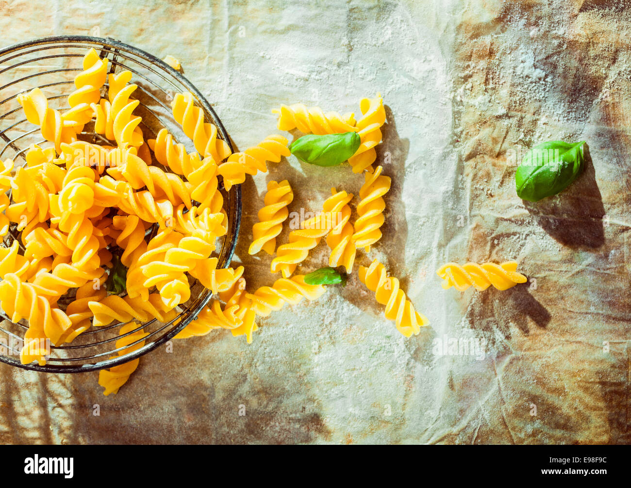Preparing an Italian fusilli pasta dish with fresh basil leaves and the traditional spiral corkscrew shaped pasta Stock Photo