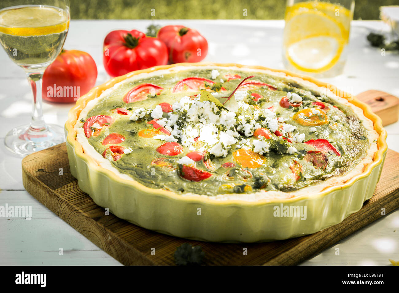 Healthy savory vegetarian quiche with egg custard, herbs, cheese and tomato served for lunch with a glass of chilled - Stock Image
