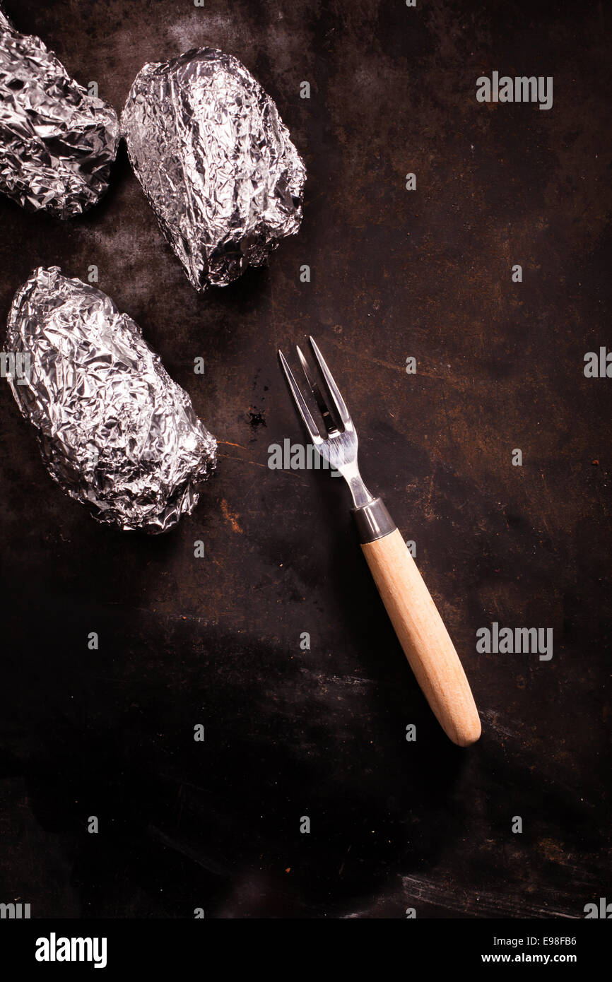 Barbecued foil wrapped potatoes still wrapped in their silver aluminium foil laying on an old slate surface with - Stock Image
