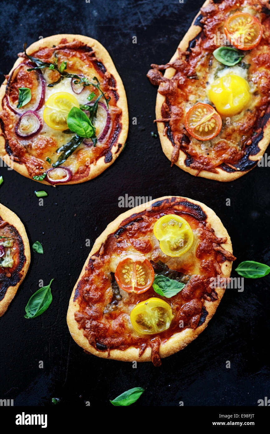 Savory mini Italian pizzas with cheese and tomato or onion, cheese and tomato toppings garnished with fresh basil, - Stock Image