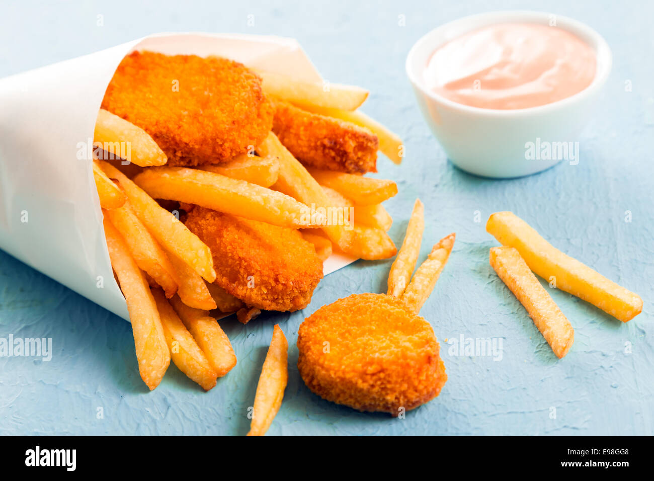Fried fish nuggets with golden French fries spilling out of a paper cone from a takeaway fish shop onto a blue surface, - Stock Image