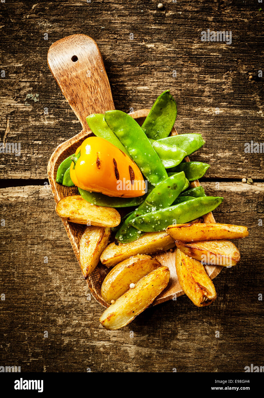 Side serving of delicious cooked vegetables served on a wooden spatula with roasted sweet red pepper, green mangetout - Stock Image